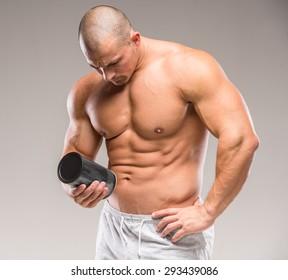Muscular bodybuilder drinking protein on a dark background.