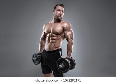 Muskulatur-Bodybuilder-Typ, der Übungen mit einer Hantel auf grauem Hintergrund durchführt