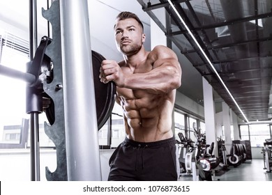Muscular bodybuilder guy doing exercises with dumbbell  on multipress in gym
