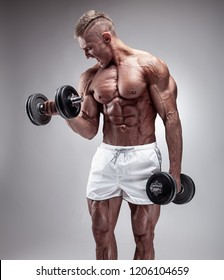 Muscular bodybuilder guy doing exercises with dumbbell over gray background