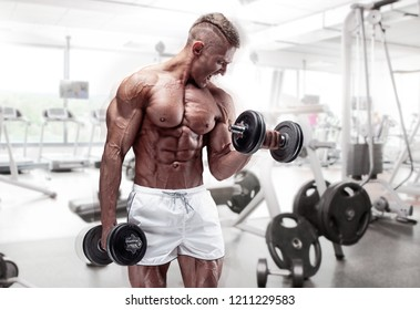 Muscular bodybuilder guy doing exercises with dumbbell at the gym