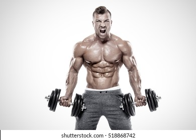 Muscular bodybuilder guy doing exercises with dumbbell over white background