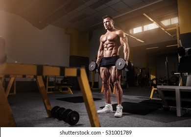 Muscular bodybuilder guy doing exercises with dumbbell in yellow gym