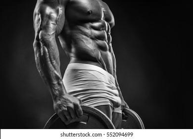 Muscular bodybuilder guy doing exercises with dumbbell disc over black background