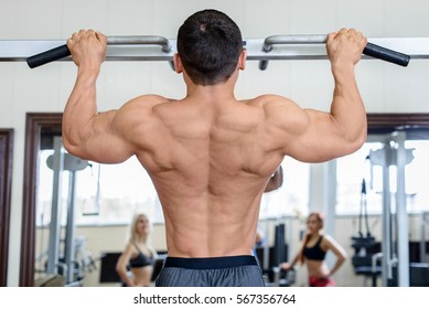Muscular bodybuilder guy doing exercises in the gym