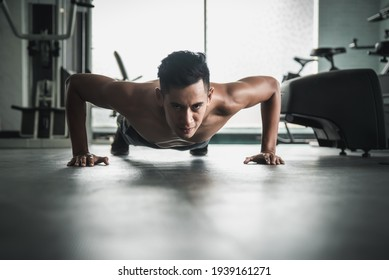 Muscular bodybuilder guy doing push ups in gym.