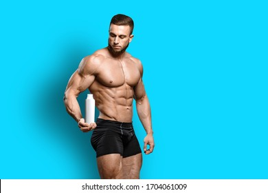 Muscular bodybuilder guy shows his perfect abs sixpack and holds sport nutrition supplement in brutal powerful hand isolated over blue background. Workout bodybuilding concept.