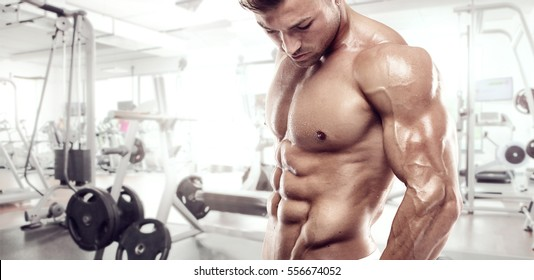 Muscular bodybuilder guy standing on gym and posing triceps muscle