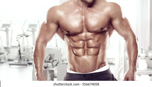 Muscular bodybuilder guy standing on gym and posing abdominal muscle