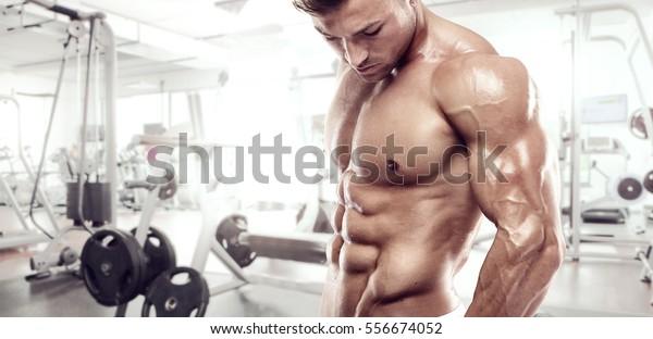 Spier bodybuilder guy staande op sportschool en poseren triceps spier