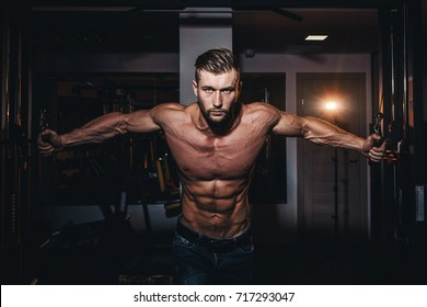 Muscular bodybuilder handsome men doing exercises in gym with naked torso. Strong athletic guy with abdominal muscles and biceps
