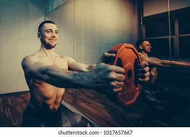 Muscular bodybuilder men doing exercises in gym naked torso. Toned image. with the mirrow view horizontal