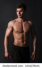 Muscular bodybuilder posing with a naked torso against a black background. Sexy man.