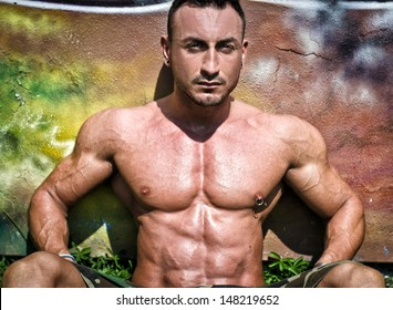 Muscular bodybuilder sitting against colorful wall showing ripped pecs and abs
