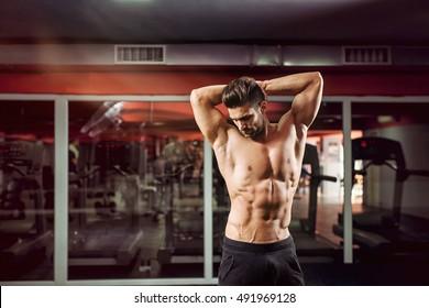 Muscular bodybuilder stretching at a gym.