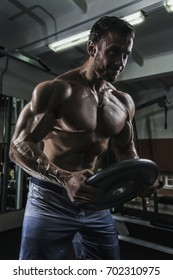 Muscular bodybuilder with the Weight plate in the dark gym