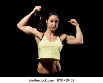 Muscular bodybuilder woman showing her muscles over black background.