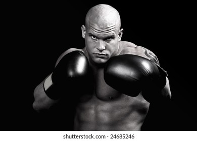Muscular boxer desaturated and isolated on black background