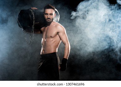 muscular boxer holding punching bag on shoulder on black with smoke
