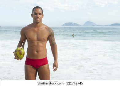 Muscular Brazilian man holding green coconut on the beach in red bathing suit smiling in Rio de Janeiro Brazil
