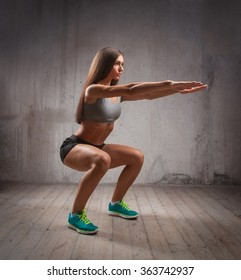Muscular brunette woman doing squats in brutal interior