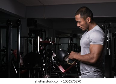 Muscular builder man with boxing gloves posing at fitness gym club