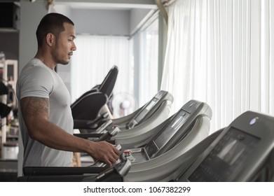 Muscular builder man running in machine treadmill at fitness gym club