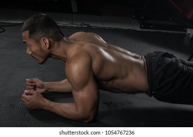 Muscular builder man training his body with doing plank exercise in Modern fitness center