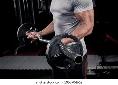 Muscular builder man training his body with barbell in Modern fitness center