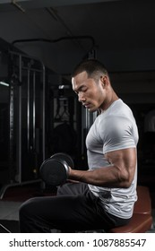 Muscular builder man training his body with dumbbell in Modern fitness center