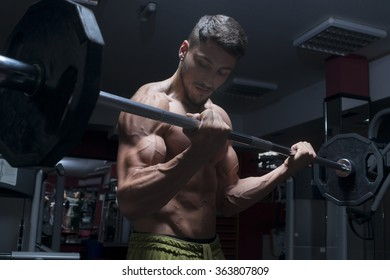 Muscular builder man training his body with dumbbell