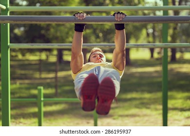 Muscular built young athlete working out in an outdoor gym