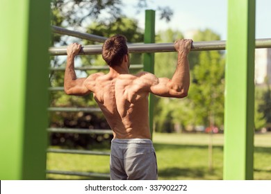 Muscular built young athlete working out in an outdoor gym, doing chin-ups