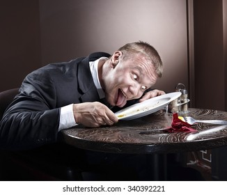 Muscular businessman eating and lick the plate
