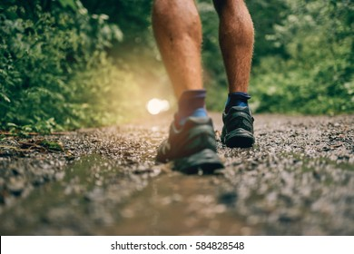 Muscular calves of fit male jogger training for cross country forest trail race in the rain on a nature trail.