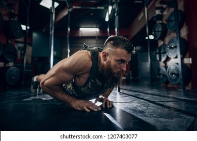 Muscular caucasian bearded man doing push-ups in military style weighted vest in gym. Weight plates in background.