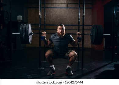 Muscular caucasian bearded man lifting weights and doing back squat in gym.