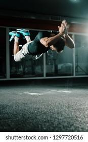 Muscular Caucasian bodybuilder doing jumping push ups in dark. Dust in the air, gym interior, mirror in background.