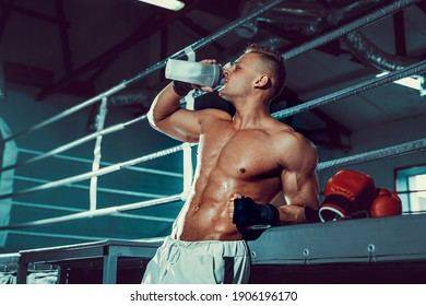 Muscular caucasian man on diet resting after boxing exercise And drinking water from shaker in the gym.