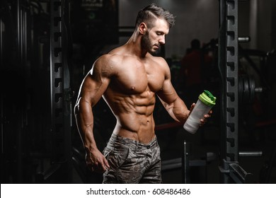 Muscular caucasian man on diet resting after exercise And drinking protein powder from shaker in the gym