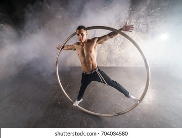 Muscular circus performer spin in the big wheel