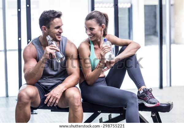 Pareja muscular discutiendo en el banco y sosteniendo una botella de agua