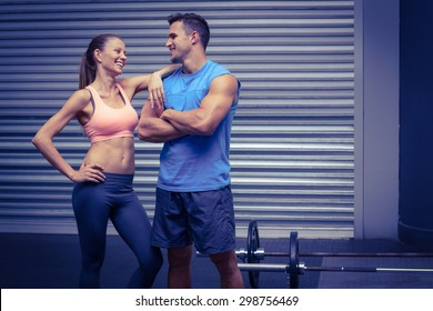 Muscular couple discussing together with arm on shoulder