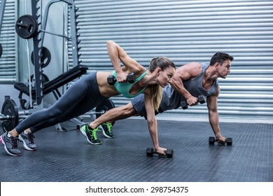 Muscular couple doing plank exercise while lifting weights