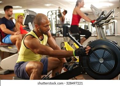 Muscular ethnic man training in gym.