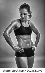 Muscular female fitness model posing in sport bra and boxers