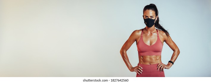 Muscular female wearing sports clothing and face mask with hands on hips against white background. Healthy woman with protective face mask.