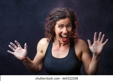 A muscular, female weight lifter with dark, curly hair, makes a funny, surprised face for the camera.  She is surrounded by chalky dust and clouds in the air.  She is backlit.