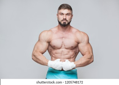 Muscular Fighter kickbox With white Bandages against the grey background
