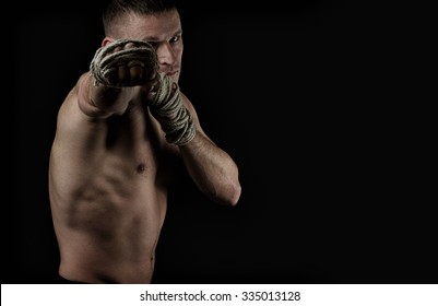Muscular fighter Muay Thai training on the black background with hemp ropes on hands. Hard light, dark lighting
